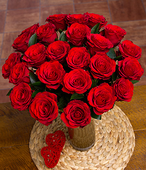 Two dozen elegant long stemmed luxury red roses complimented by enhancing Ruscus leaf greenery.
