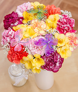 ../A beautiful arrangement of Carnations and scented yellow Freesia with three keepsake jewelled butterfly picks.