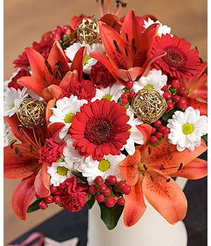 ../A gorgeous display of red Lilies, Germini and spray Carnations with festive berries and woven balls.
