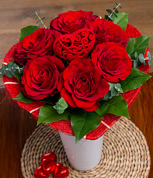 A gorgeous gift of six Upper Class Red Roses together with a keepsake heart pick in a red Sisal heart.