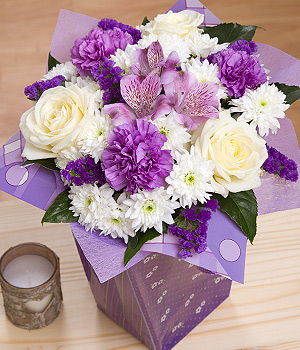 ../Gorgeous Avalanche Roses, purple Carnations and purple Alstroemeria delivered in a cute purple gift bag.