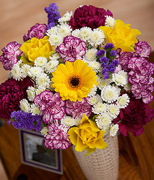 ../A bright and cheerful arrangement featuring purple Carnations, yellow Roses and blue Statice.