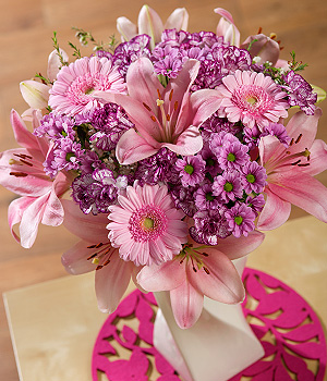 ../An eye-catching display of pink Lilies, Spray Carnations, pink Germini and delicate white Wax Flower.