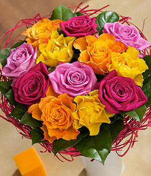../12 mixed Roses in pink, orange, yellow and cerise shades, beautifully framed with Salal and rattan.