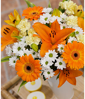../A colourful cocktail of summer shades with orange Germini, orange Lilies and yellow Spray Carnations.